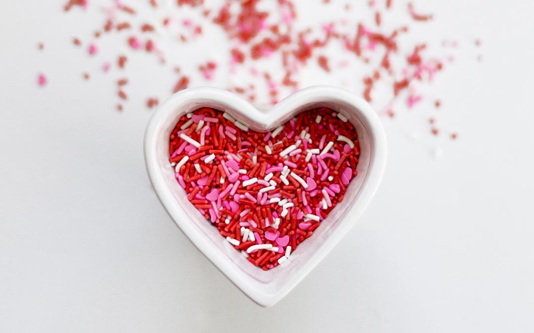 Red and pink sprinkles in a heart shaped bowl as part of the history of Valentine's Day.